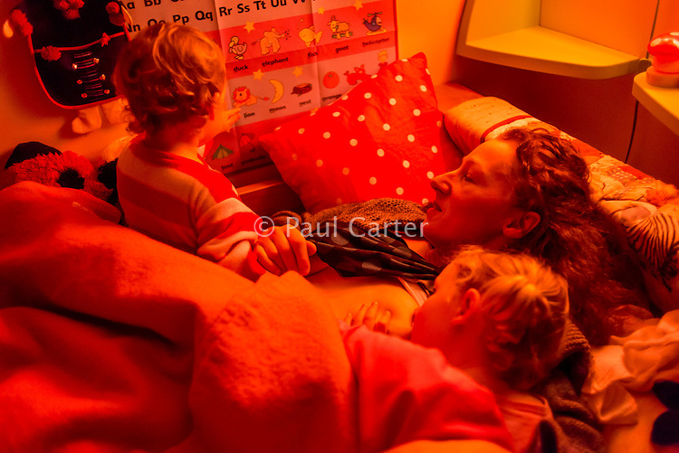 A woman breastfeeds her 4 year old daughter off to sleep at bedtime while chatting with her 20 month old toddler.<br /> <br /> 07/02/2013<br /> Hampshire, England, UK