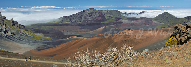 Male and female adult hikers on the Sliding Sands trail in HALEAKALA NATIONAL PARK on Maui in Hawaii USA