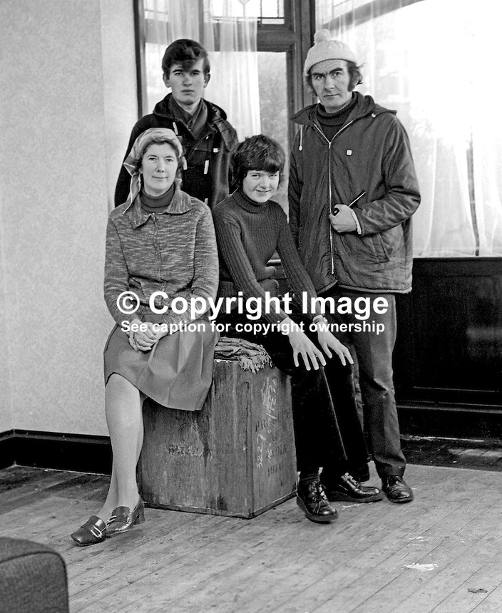 Rev Joseph Parker and wife, Dorothy, and their son, Roger, and daughter, Karen, in their almost empty Belfast home prior to emigrating to Canada. Rev Parker founded the Witness for Peace Movement following the death of their son in an explosion. Taken 28th January 1975. Ref: 197501280054a.<br /> <br /> Copyright Image from Victor Patterson, 54 Dorchester Park, Belfast, UK, BT9 6RJ<br /> <br /> t1: +44 28 9066 1296 (from Rep of Ireland 048 9066 1296)<br /> t2: +44 28 9002 2446 (from Rep of Ireland 048 9002 2446)<br /> m: +44 7802 353836<br /> <br /> e1: victorpatterson@me.com<br /> e2: victorpatterson@gmail.com<br /> <br /> The use of my copyright images is subject to my Terms &amp; Conditions.<br /> <br /> It is IMPORTANT that you familiarise yourself with them. They are available on my website at www.victorpatterson.com.<br /> <br /> None of my copyright images may be used on a website unless they are visibly watermarked, i.e. &copy; Victor Patterson within the body of the visible image. Metadata denoting my copyright must NOT be deleted. <br /> <br /> Web use is extra at currently recommended NUJ rates.