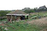 NKANDLA, SOUTH AFRICA - OCTOBER 9: An view of a damaged hut next to the fence to South Africa president Jacob Zuma's new private residence in his birth village on October 9, 2012 in KwaNxamalala, Nkandla. South Africa.  The South African government is spending R240-million (about US$ 27 million) to construct the vast property for his large family. (Photo by Per-Anders Pettersson)