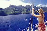 Woman pointing out waterfall on the Na Pali Coast, aboard 'Heron', a Halberg-Rassy 46 sailboat, Kauai, Hawaii