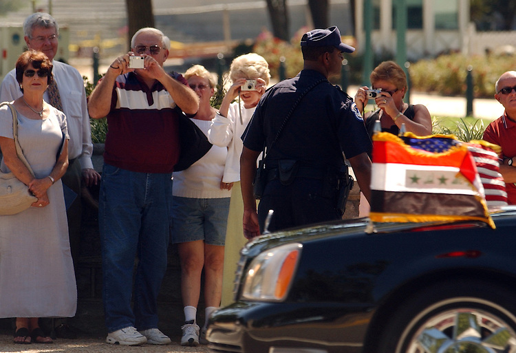 Tourists watch the arrival of the president of Iraq Jalal Talabani's motorcade, before a meeting with Congressional Leaders.