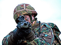 British Army soldier on armed foot patrol on the streets of Northern Ireland. He is using the telescopic sites on his SA80 rifle to enable him to provide cover for one of his collegues. This image may only be used to portray the subject in a positive manner..©shoutpictures.com..john@shoutpictures.com