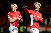 Lyle Taylor of Charlton Athletic celebrates their victory with George Lapslie and then points to the scoreboard as he likes the look of some of the results in Division One during Charlton Athletic vs Burton Albion, Sky Bet EFL League 1 Football at The Valley on 12th March 2019
