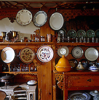 Plates, glasses, china and tagines displayed on carved wooden shelves
