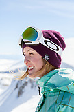 USA, California, Mammoth, a female snowboarder smiles and laughs while taking a break on a run at Mammoth Ski Resort