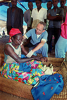 Dr. Doyt Conn, Rochester, Minn., diagnoses a patient with a dislocated shoulder after she was kicked by a cow at the AmeriCares clinic in Buranga Rwanda three months after the end of the genocidein 1994. The New Canaan, Conn.,  humanitarian organization ran the clinic from August to Dec., 1994 to help refugees returning from camps in Goma, Zaire (now Congo). The clinic also treated any who came for help with many problems, frequently related to the collapse of infrastructure which provided for basic needs. The country was ravaged by genocide and civil war in 1994.