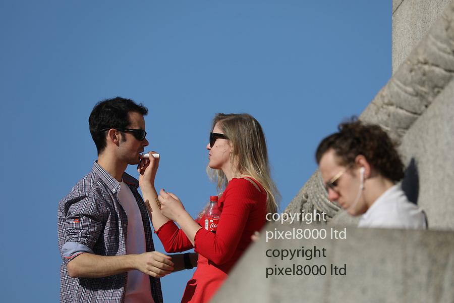 Hot Weather February 2019<br /> Lovers make out and laugh, joke and apply lip salve on Nelson's Column in Trafalgar Square with National Gallery in the background.<br /> <br /> <br /> <br /> <br /> picture by Gavin Rodgers/ Pixel8000<br /> 27.2.19