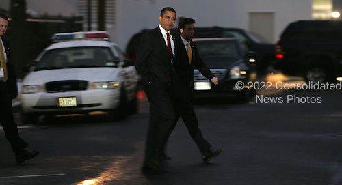 Washington, DC - January 27, 2009 -- United States President Barak Obama walks across West Executive Avenue in the White House to attend a swearing in ceremony in the Eisenhower Office Building on Tuesday, January 27, 2009.  Walking next to President Obama is White House press advance staffer, Brian Mosteller. .Credit: Dennis Brack - Pool via CNP