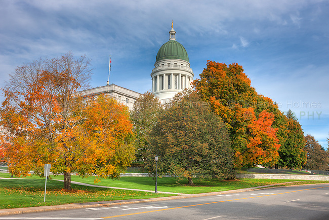 The Maine State House in Augusta, Maine accented by the changing leaves of fall foliage.