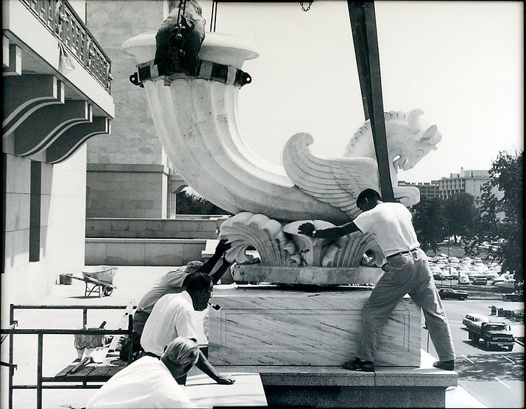 In 1964 during the finial construction phase workers place a Rhython in front of the Rayburn House Office Building.
