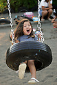 "A three-year-old girl plays at Nishi Rokugo Koen in Tokyo on September 6, 2009. The ""Tire Park"" is filled with big tires in every combination, like robots, dragons, tire swings, bridges, tunnels, montains and slides. Approximately 3,000 old tires are used to set up the playground covered completely with sand. (Photo by Laurent Benchana/Nippon News)"
