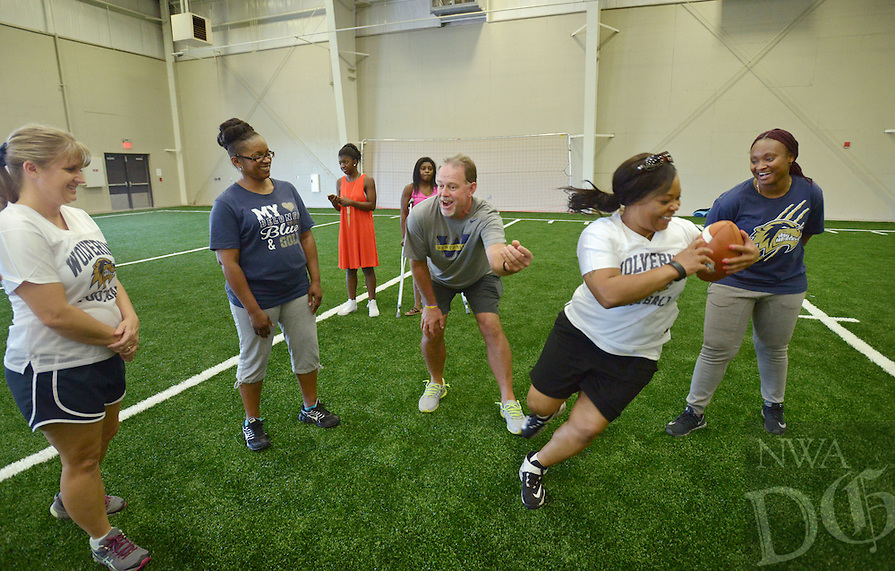 NWA Democrat-Gazette/BEN GOFF @NWABENGOFF<br /> Kyle Marr, Bentonville West receivers coach, shows Lola Brundage (second from right), mother of Bentonville West sophomore defensive tackle Kristian Dotson, how to carry a football securely on Sunday Aug. 21, 2016 during Wolverine Helmets and Heels at Bentonville West High School in Centerton. The event was an oportunity for mothers and other female relatives of Bentonville West football players to meet coaching staff and learn more about the game.