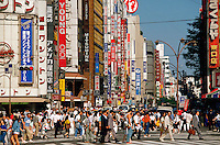A Japanese street scene of crowds in the Shinjuku district. Tokyo, Japan.