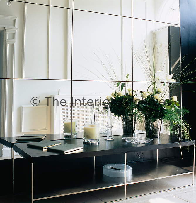 A dramatic flower arrangement and glassware peices are displayed on a low black wood and steel coffee table. The wall behind is mirrored and gives a sense of space to the room.
