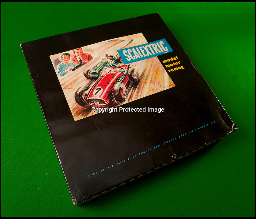 BNPS.co.uk (01202 558833)<br /> Pic: PhilYeomans/BNPS<br /> <br /> The original Scalextric.<br /> <br /> Blast from the past - 56 year old box of the very first Scalextric finally handed over to inventors daughters.<br /> <br /> The dying wish of Scalextric inventor Freddie Francis has been granted - after his daughters were gifted an original mint set that has been in storage for the past 50 years.<br /> <br /> Freddie and his widow Diane boxed up the original set shortly before he died in 1998 and Diana has waited till now before handing the valuable heirloom over.<br /> <br /> The previously unopened set has been preserved in a wooden box at the Francis family home until now.<br /> <br /> The historic set contains 1950's Ferrari and Maserati style racing car's that would have been driven by Fangio and Stirling Moss and even includes oil to keep the cars running and silicone for 'skid patches'.<br /> <br /> Although the set cost &pound;5 in 1957, it's worth well over &pound;1500 today.