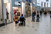 Woman in a mobility electric wheelchair with her dog for the disabled inside Banbury Castle Quay shopping centre Oxfordshire UK..©shoutpictures.com..john@shoutpictures.com.