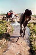 1970, Punjab, India --- A farmer diverts water from an irrigation channel near the Bhakra dam in the Punjab. --- Image by © JP Laffont