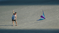 A man flies a kite in afternoon shadows at Virginia Beach, Va.