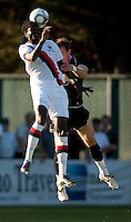 Manchester City midfielder Emmanuel Adebayor heads the ball as Portland Timbers defender Ross Smith defends during a match at Merlo Field in Portland Oregon on July 17, 2010.