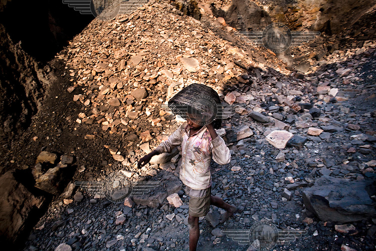 A young boy returning to collect a fresh load after carrying out coal from an open cast minenear Bokapahari village. Coal fires rage just below the surface of the ground, making it too hot to walk with naked feet. Noxious gases spew up from fissures, rendering the environment toxic. Residents who live above the furnace make $2 a day collecting small chunks of coal that they sell to illegal middlemen. One or two houses collapse annually into vast underground caverns left unfilled by abandoned mining operations.