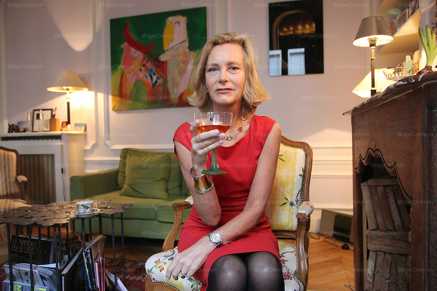 Marie de Tilly poses with a glass of porto in her apartment..Marie de Tilly gives lessons on French Etiquette. She lives in a bijou Hausman apartment in central Paris, not far from the Champs Elysées. She has trained people with these skills for several years; working across the Paris area and even takes her work worldwide, giving classes to a range of people. She is especially popular in Russia and the ex-Soviet countries such as Kasakhstan. Her skills are sought after by individuals, families and businessmen wishing to aspire to enter French High Society. Her students, whether they are Russian or French, want to learn the necessary airs and graces to blend seemlessly into Parisian haute societé. Paris, France