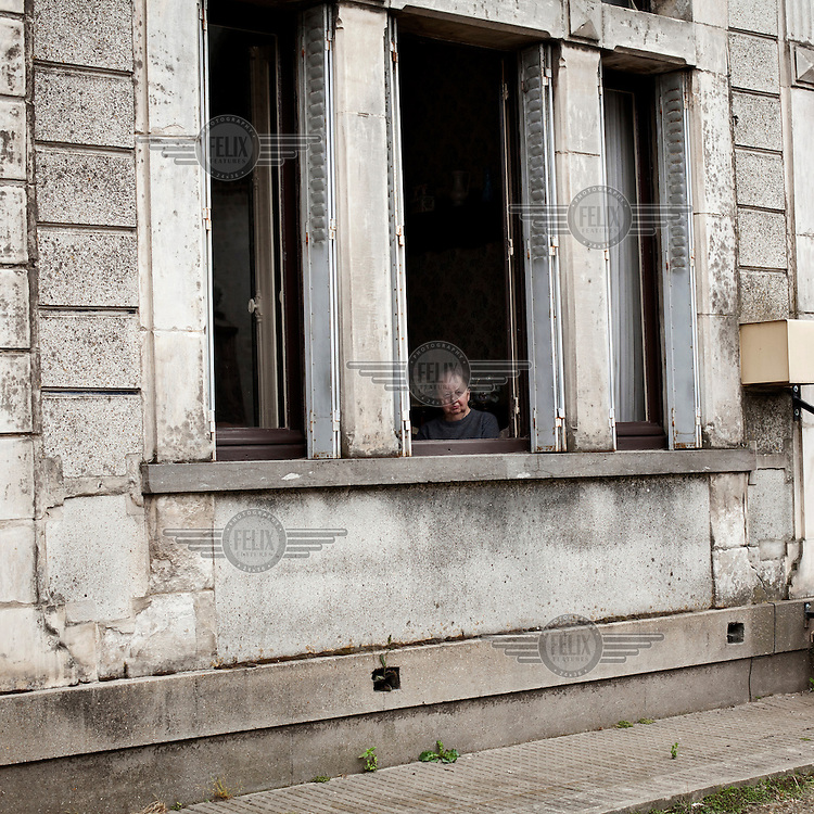A man looks out of a window, waiting for Tour de France to pass through their village..