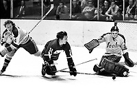 Vancouver Canucks #11 Wayne Maki tries to score on Seals Dick Redmond and goalie Gilles Meloche..(1971 photo/Ron Riesterer)