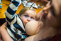 A mother breastfeeds her two year old daughter in the family restaurant and play area of a pub.<br /> 