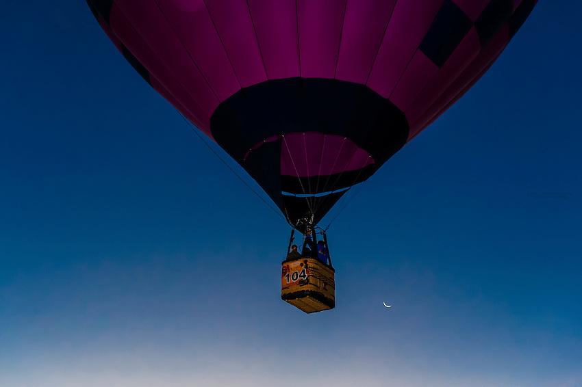 Hot air balloons lifting off from Balloon Fiesta Park in predawn light, Albuquerque International Balloon Fiesta, Albuquerque, New Mexico USA.