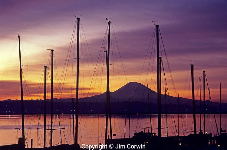 Sunrise over Lake Washington with Cascade Mountain range and marina with dramatic clouds and silhouetted masts Seattle Washington State USA
