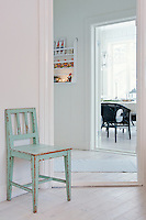 As the only note of colour in the hallway, the pale mint green of this chair, with its distressed patina, becomes a bold feature against the white walls and floors