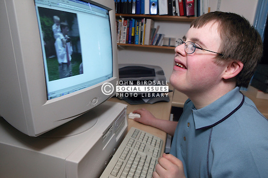 Teenage Downs Syndrome boy using a computer,