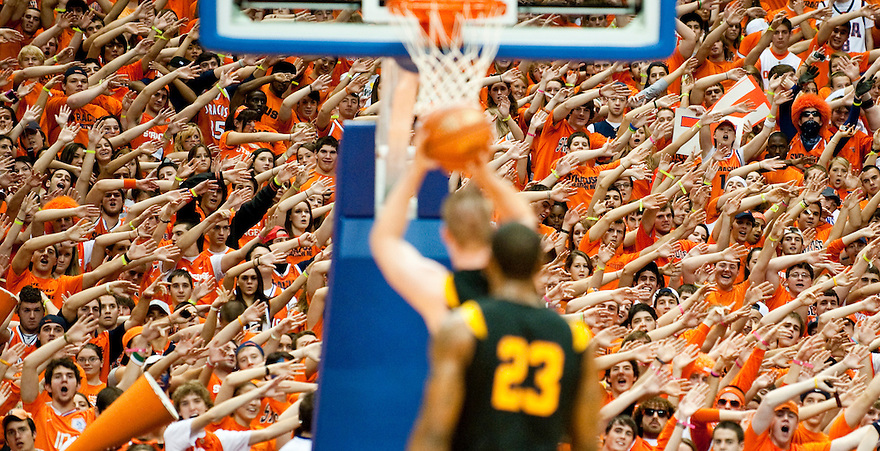 Otto's Army, the student fan section, attempts to distract Albany's Brett Gifford (54) from successfully making his free throw shot while teammate Tim Ambrose stands nearby (23). Syracuse defeated Albany 75-43 and sealed the win as Head Coach Jim Boeheim's 800th win.