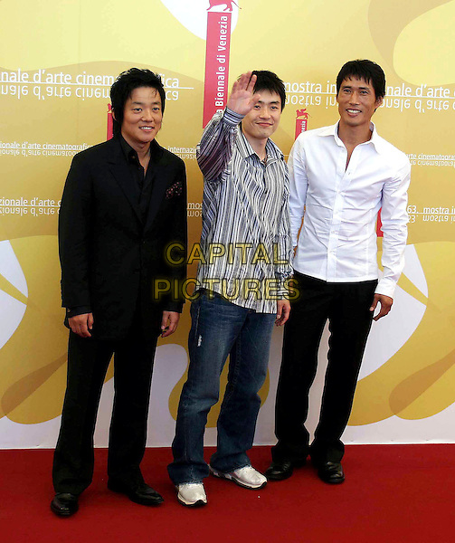 "RYOO SEUNG-WAN, JUNG DOO-HONG & LEE BEOM-SO.""Jjakpae"" photocall on the third day of the 63rd Venice International Film Festival, Venice, Italy..September 1st, 2006.Ref: OME.full length hand waving striped stripes shirt white black trousers jeans denim.www.capitalpictures.com.sales@capitalpictures.com.©Omega/Capital Pictures"
