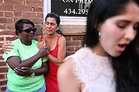 From left, Stephanie Whindleton and Abby Guskin embrace as Katherine Nies sings a hymn during a large vigil for Heather Heyer Sunday night at 4th Street SE and Water Street in Charlottesville, Va. Heyer was killed and 19 others injured when a car intentionally ran through a crowd of counter protestors after the Unite The Right rally. Photo/Andrew Shurtleff/The Daily Progress