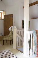 A sturdy wooden staircase has been given a subtle lime wash to blend with the white walls
