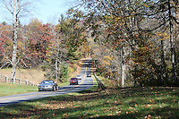 Stock photo - cars passing by on a sloped road on Blue Ridge Parkway, surrounded with fall trees North Carolina in America.