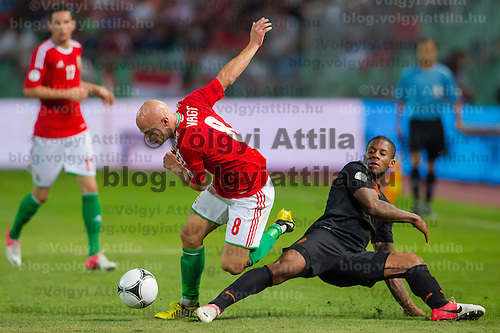 Hungary's Jozsef Varga (C) and Netherlands' Jeremain Lens (R) fight for the ball during a World Cup 2014 qualifying soccer match Hungary playing against Netherlands in Budapest, Hungary on September 11, 2012. ATTILA VOLGYI