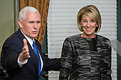 United States Vice President Mike Pence gestures toward attendees after swearing in Betsy DeVos, U.S. Secretary of Education, right, in the Vice President's Ceremonial Office in Washington, D.C., U.S., on Tuesday, Feb. 7, 2017. DeVos squeaked through a history-making Senate confirmation vote to become U.S. education secretary, as Vice President Mike Pence broke a 50-50 tie and Republicans staved off last-minute defections that would have killed her nomination. <br /> Credit: Andrew Harrer / Pool via CNP