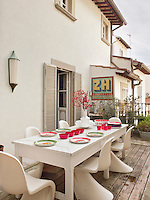 A white painted table and Arne Jacobsen chairs are set outside on a courtyard patio. Red and green tableware provide a vibrant colour contrast.