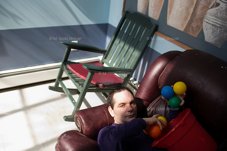 Michael Martin plays with balls after lunch in the residences in Malone Park at the Fernald Developmental Center in Waltham, Massachusetts, USA.  Michael, 52, cannot speak.