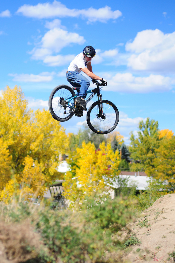 "A mountain biker bmx dirt jumping at the ""Sunset trails"" in Lakewood, Colorado on October 19, 2008. sunset trails"