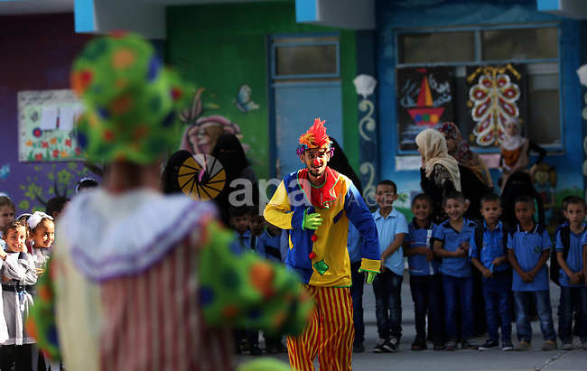 Palestinians dressed in costumes perform to amuse schoolchildren on the first day of a new school year, at a United Nations-run school in Deir al-Balah refugee camp in the central Gaza Strip August 23, 2017. Photo by Ashraf Amra