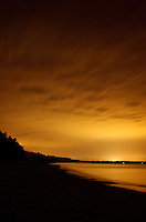 The orange glow of Marquette, MI illuminates the clouds and Lake Superior shoreline.