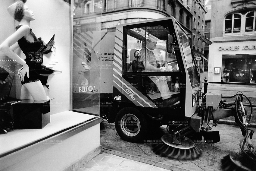 Switzerland. Geneva. Garbage collectors. Streets cleaning. A street sweeper  drives on the sidewalk a street brooming machine. The worker and its machine pass by the Beldona shop, selling sexy attractive underwears and bras for women. © 1991 Didier Ruef