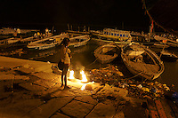 girl selling flowers for puja (prayer) at river Ganga takes a break in a night of Diwali festival time (festival of lights)