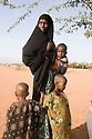 Kenya - Dadaab - 22nd July 2011. Young mother queing for food distribution with her 3 children at Ifo camp.