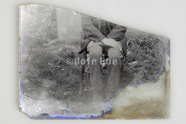 part of a broken glass plate with portrait of man sitting on a chair