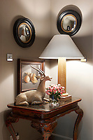 A pair of convex mirrors hangs above a table displaying a carved antelope and a vase of flowers